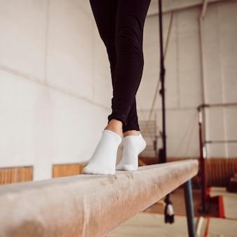 Pernas de mulher atlética treinando na trave de equilíbrio