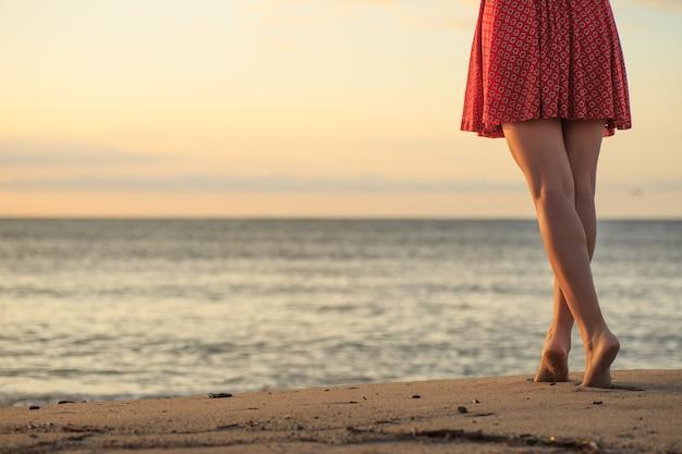 Pernas de mulher bonita, caminhando na praia.