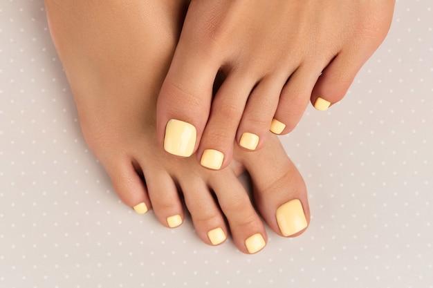 Pernas de mulher bonita com desenho de unhas de verão na superfície cinza de bolinhas