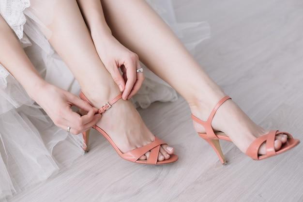 Pernas de mulher bonita em sapatos de salto alto. vestido e sapatos de noiva. manhã da noiva