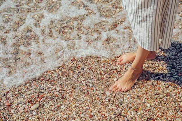 Pernas de mulher bonita na praia de calhau com água do mar espumosa