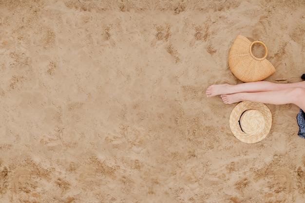 Pernas de mulher bronzeada com chapéu de palha e bolsa na praia de areia