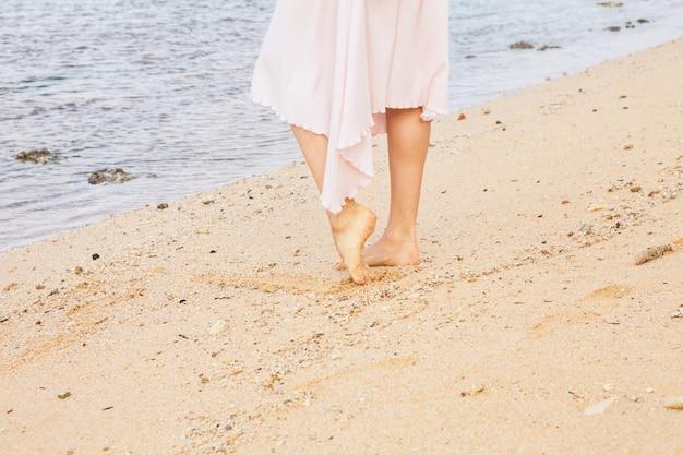Pernas de mulher caminhando na areia da praia