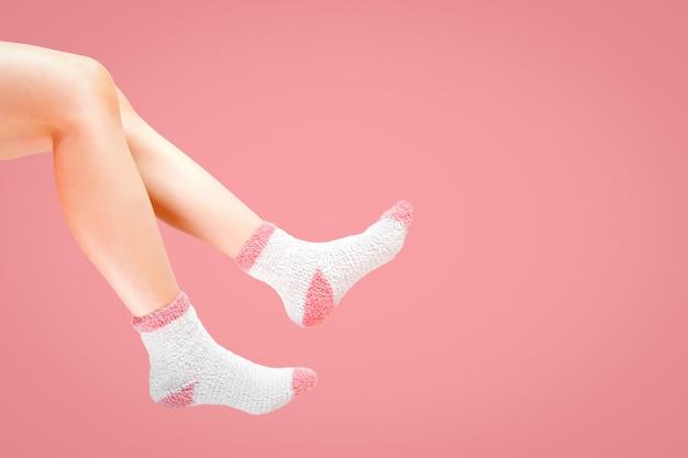 Pernas de mulher com meias de moda em fundo rosa.