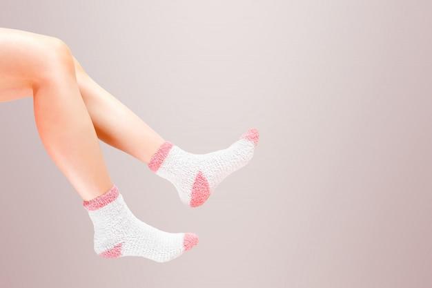 Pernas de mulher com meias de moda no fundo.