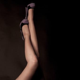 Pernas de mulher com os sapatos no preto