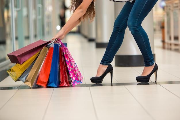 Pernas de mulher com sacos de compras