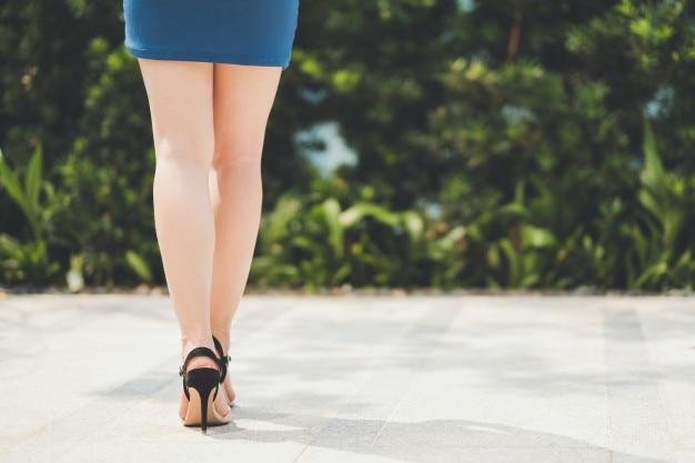 Pernas de mulher com saia curta e salto alto