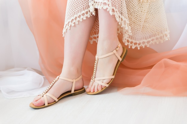 Pernas de mulher com sapatos boho no interior