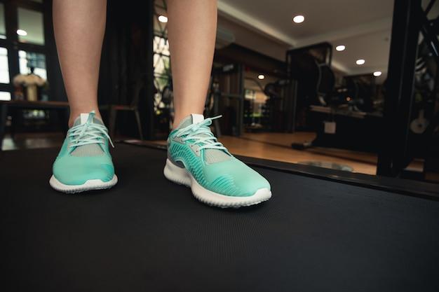 Pernas de mulher com tênis esportivos, correndo na esteira no ginásio de fitness.