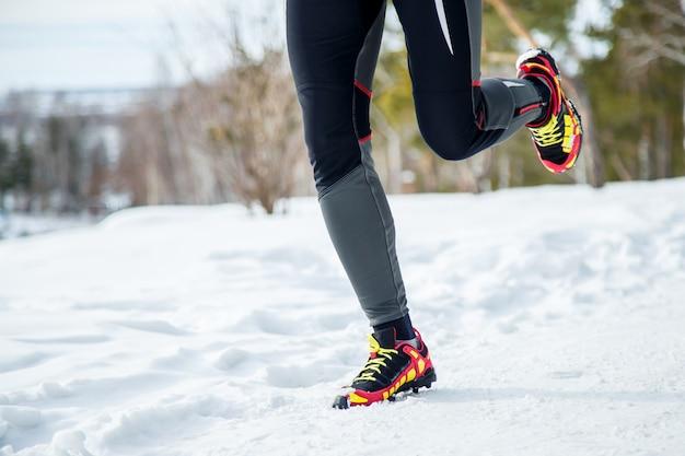 Pernas de mulher correndo ao ar livre em dia de inverno