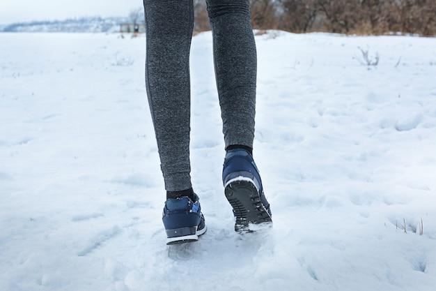 Pernas de mulher correndo ao ar livre no dia de inverno