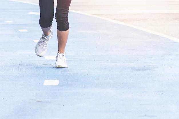 Pernas de mulher correndo na pista de corrida azul.