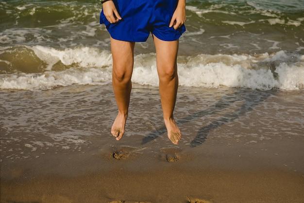 Pernas de mulher de vestido azul pulando na costa da praia