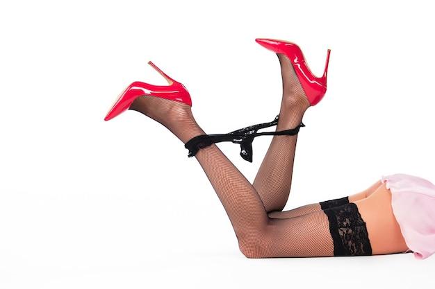 Pernas de mulher deitada. calcinha preta e salto vermelho.