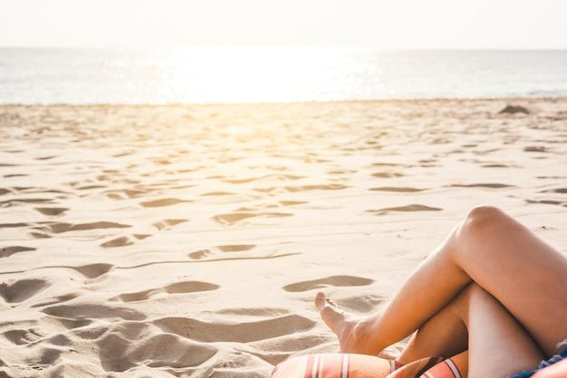 Pernas de mulher descansando e relaxando na praia. metade inferior do corpo da menina deitada na praia