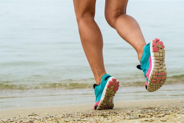 Pernas de mulher desportiva na praia