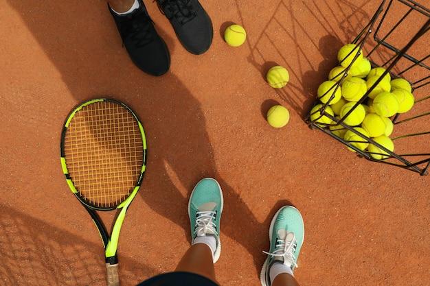 Pernas de mulher e homem de tênis em quadra de saibro com bolas de tênis e raquete