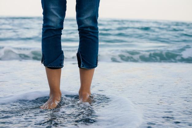 Pernas de mulher em jeans azul em pé na água do mar na costa