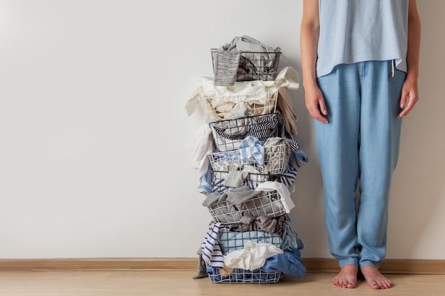 Pernas de mulher em pé perto de um cesto de roupa suja de metal cheio de roupa suja e linho.