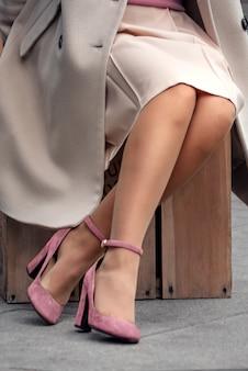 Pernas de mulher em sapatos rosa com salto alto