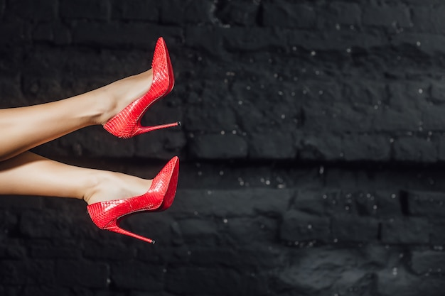 Pernas de mulher em sapatos vermelhos no ar