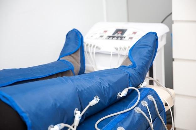 Pernas de mulher em uma capa especial no salão de beleza. tratamento corporal alternativo. massagem anti-gordura pressoterapia.