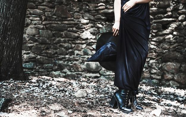 Pernas, de, mulher, em, vestido longo, segurando, chapéu bruxa