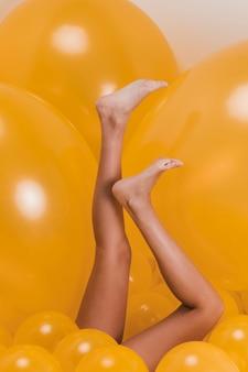 Pernas de mulher entre muitos balões amarelos