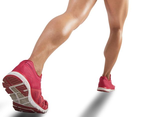 Pernas de mulher esportiva correndo, isoladas no branco