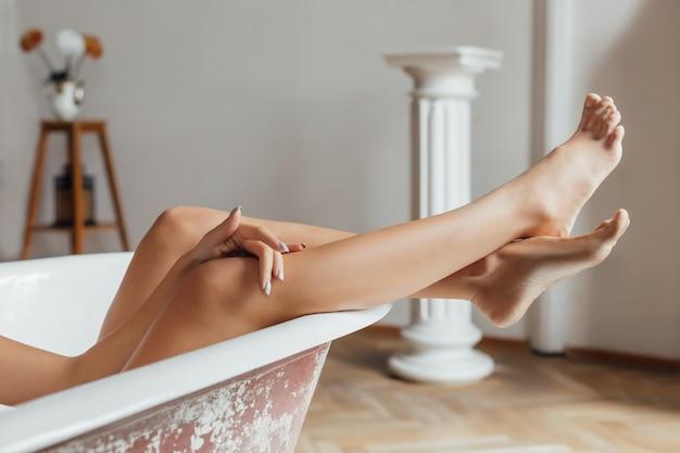 Pernas de mulher jovem com pele lisa após depilação a laser