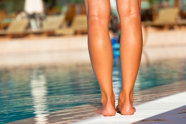 Pernas de mulher jovem em pé na beira da piscina