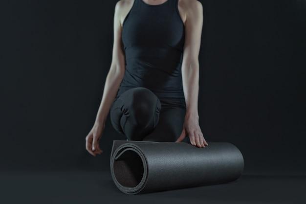 Pernas de mulher jovem praticando ioga e tapete de ioga em um fundo preto escuro. copie o espaço. vista frontal