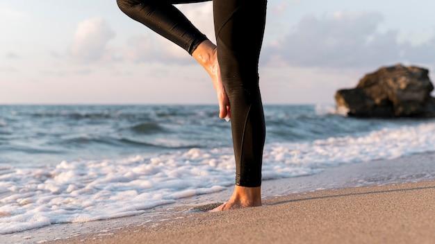 Pernas de mulher meditando na praia