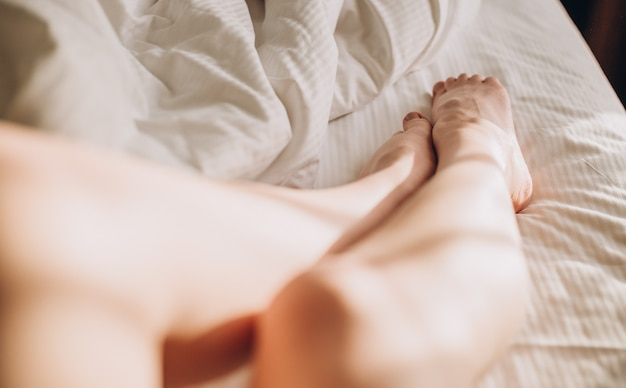 Pernas de mulher na cama com roupa de cama branca, raios de sol. imagem recortada de eroticamente deitada na cama linda mulher no quarto.