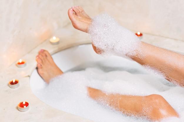 Pernas de mulher na espuma do banho. relaxamento no spa.