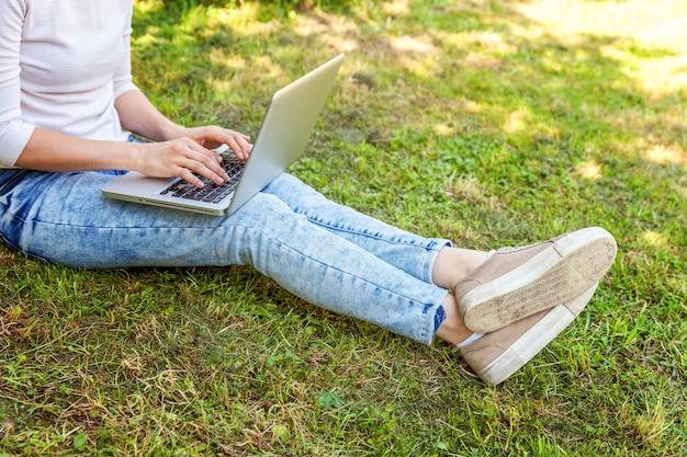 Pernas de mulher na grama verde no parque da cidade, mãos trabalhando no computador portátil