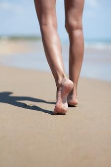 Pernas de mulher na praia do mar de areia