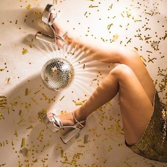 Pernas de mulher no chão de festa com a luz da bola de discoteca