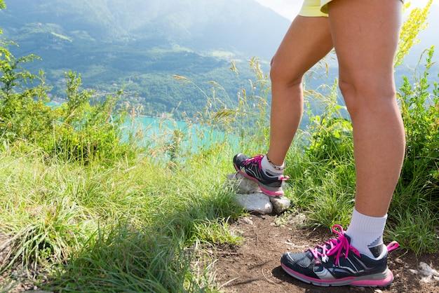 Pernas de mulher saudável na rocha da montanha
