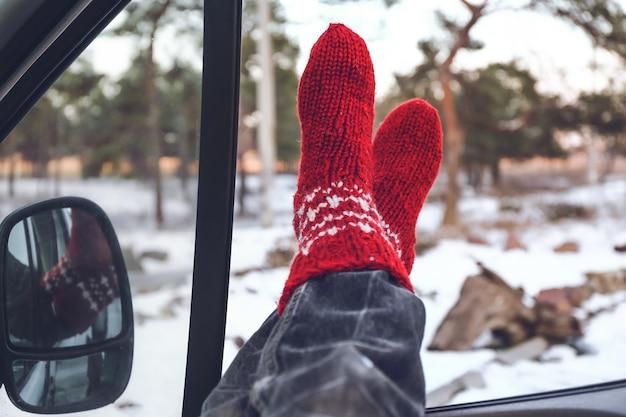 Pernas de mulher sentada no carro num dia de inverno