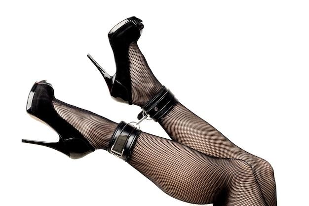 Pernas de mulher sexy de salto alto bondage e meias arrastão isoladas no fundo branco