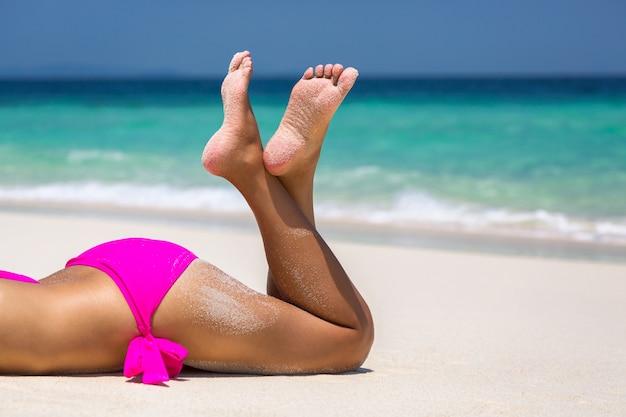Pernas de mulher sexy em biquíni rosa