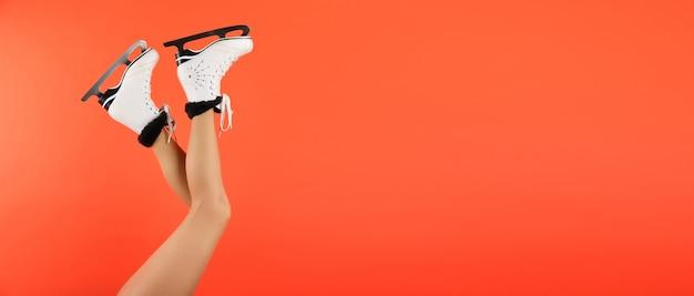 Pernas de mulher usando patins de gelo levantadas