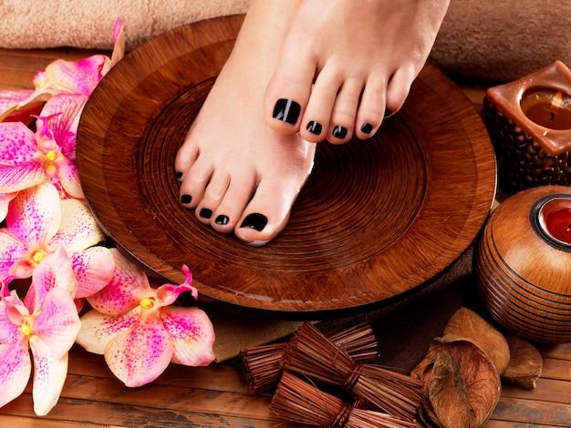 Pernas de mulheres bonitas com pedicure preta após procedimentos de spa - conceito de tratamento de spa