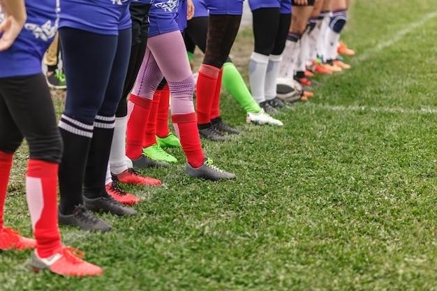 Pernas de mulheres de rúgbi alinhadas no campo