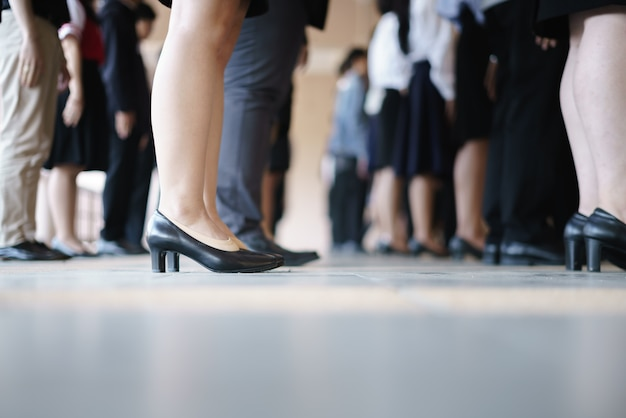 Pernas de negócios e mulher esperando em uma fileira