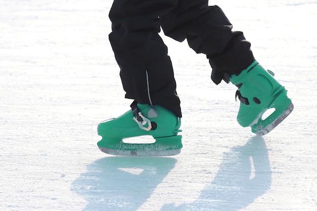 Pernas de patins em azul na pista de gelo. esporte e entretenimento. descanso e férias de inverno.