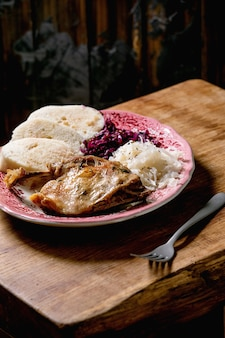 Pernas de pato assado com knedliks de pão cozido fatiado, chucrute vermelho e branco em prato de cerâmica sobre mesa de madeira marrom. cozinha tradicional checa, alemã e europeia