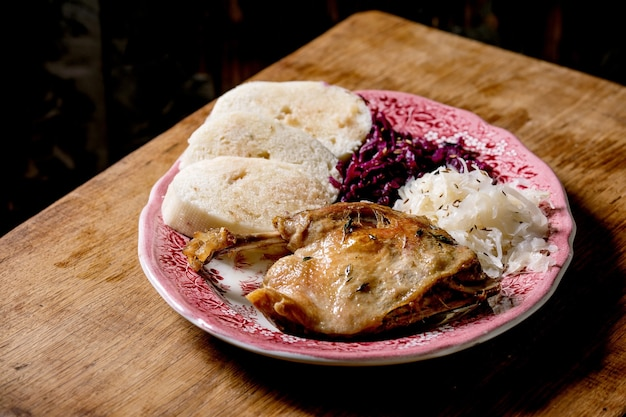 Pernas de pato assado com knedliks de pão cozido fatiado e chucrute em prato de cerâmica sobre mesa de madeira marrom. cozinha tradicional checa, alemã e europeia